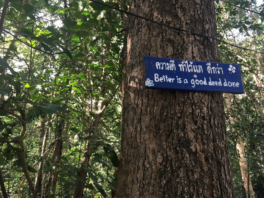 """Sign along forest path to Wat Umong that says """"Better is a good deed done"""" in Chiang Mai, Thailand"""