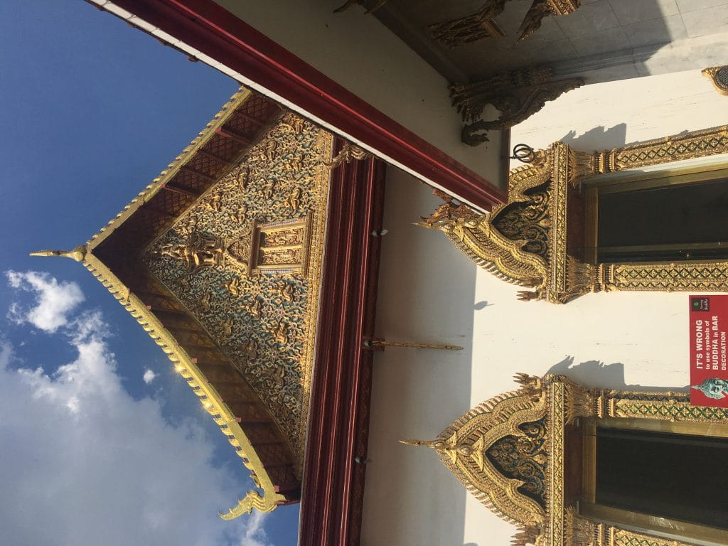 Wat Chana Songkram exterior temple walls. One of the many golden roofs.