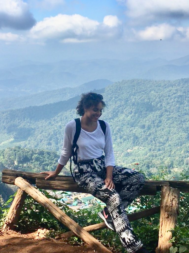 Me sitting on a bench at a beautiful viewpoint of rolling mountains and blue skies in Chiang Mai, Thailand.