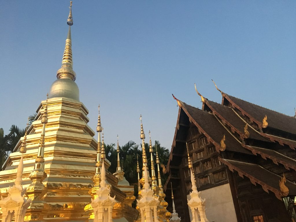 Photo of shining gold stupa and temple at sunset Wat Phan Tao in Chiang Mai, Thailand
